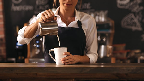 woman pouring milk in coffee