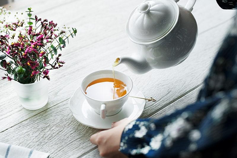 woman pouring hot tea